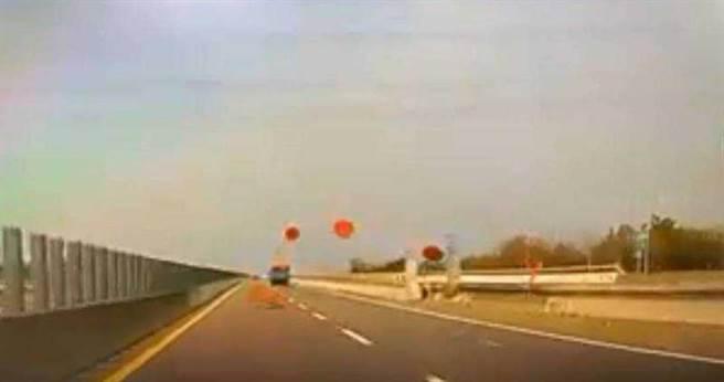 總計10個辦桌用的大型紅色圓桌不斷從貨車車斗噴飛,而貨車駕駛似乎沒有察覺,仍不斷向前開,大圓桌就這樣四散在道路上。(圖/取自臉書社團《爆料公社》)