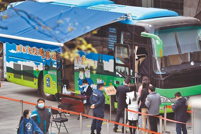 大陸疫苗接種率還不到1成,讓新華社發文呼籲民眾接種。圖為9日北京西單商業區的移動疫苗接種車前,民眾排隊等待接種。(中新社)