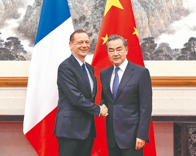 中国国务委员兼外长王毅(右)9日与法国总统外事顾问博纳通话。图为2人2019年7月在北京会面。(新华社)