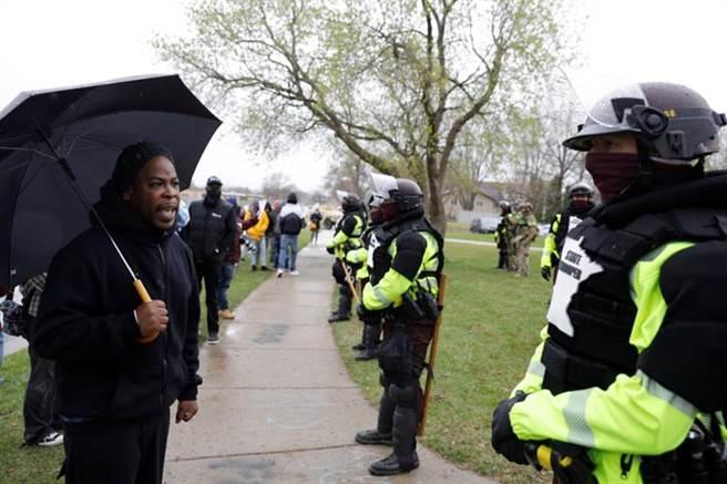 美明尼蘇達警烏龍槍殺20歲非裔男,民眾在警察局外與警員對峙。(圖/路透)