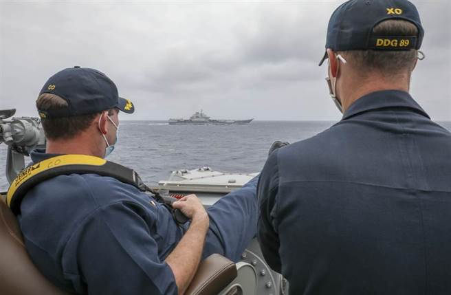 「馬斯廷」號(USS Mustin,DDG-89)驅逐艦艦長羅伯特·布里格斯(Robert J. Briggs,左)4日翹著雙腿,和副艦長斯萊(Richard D. Slye)從艦橋操舵室外監視數千公尺外的解放軍航母「遼寧」艦。(美國海軍)
