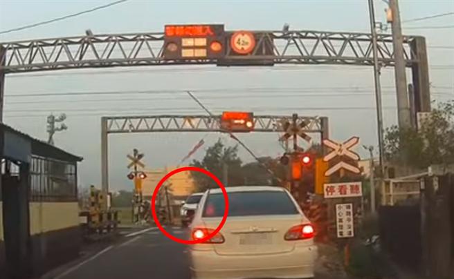 駕駛見遮斷桿已升起就往前開,沒想到遮斷桿又再次放下,導致轎車當場卡在平交道。(圖/翻攝自爆料公社影片)