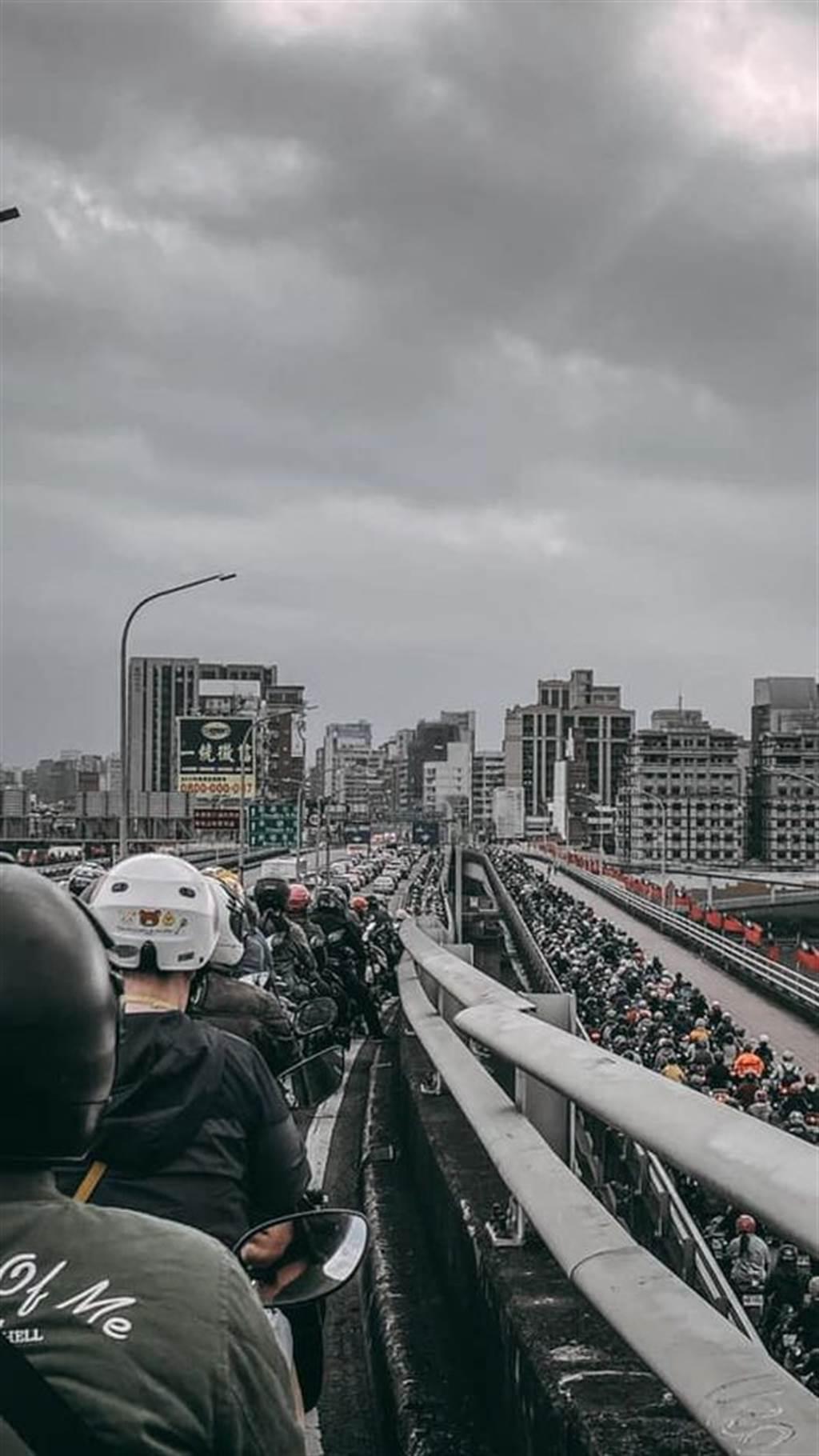 通勤時間的台北橋被機車塞得水洩不通,最扯的是,連右下方的另條路面也被機車給佔據,整個台北橋看起來就像是座大型的停車場。(圖/網友張哲瑋提供)