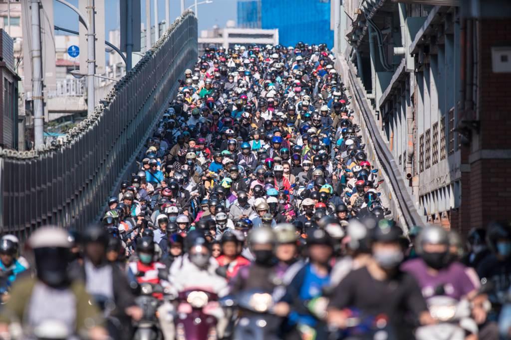 在上下班尖峰時間,台北橋形成的「機車瀑布」多次登上國際版面,甚至被日本綜藝節目評為台灣絕景。(圖/Shutterstock)