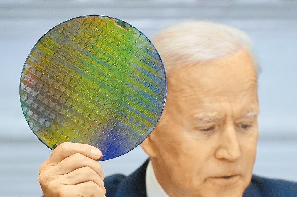 美國總統拜登12日在白宮半導體峰會上拿起一片晶圓,強調晶片供應鏈對美國至關重要。(美聯社)