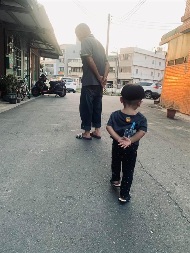 一名網友分享照片指出,阿公帶的孩子,應該都會這樣走路吧!只見爺孫倆散步時的動作如出一轍,都不自覺將雙手放在腰後。(圖/翻攝自爆廢1公社)