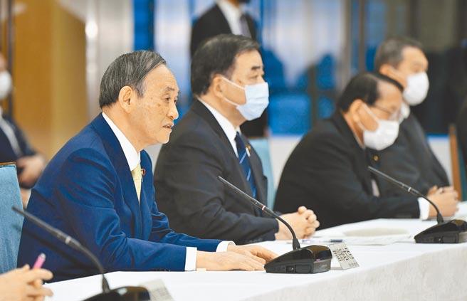 日本政府於13日上午召開的內閣會議決定,福島核汙水經過濾及稀釋後,將排入大海。圖為日本首相菅義偉(左)在官邸舉行內閣會議。(美聯社)