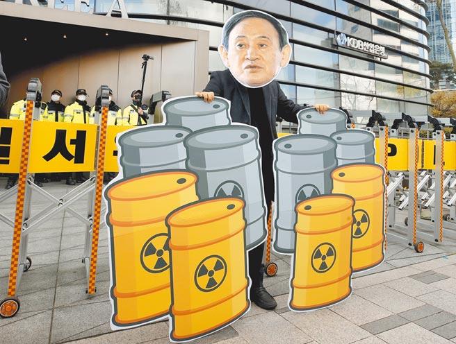 一名韓國青年戴著日本首相菅義偉的面具,在首爾街頭抗議日本決定將核汙水排入大海。(美聯社)