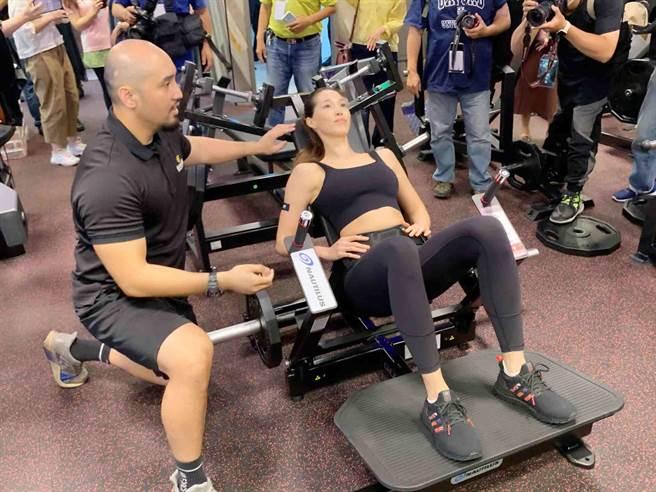 健身工廠企業總部打造2層樓健身房給員工使用,代言人Akemi示範器材。(柯宗緯攝)