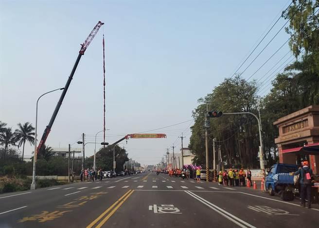 一家起重机公司用挂手悬挂20公尺高鞭炮。(周丽兰摄)