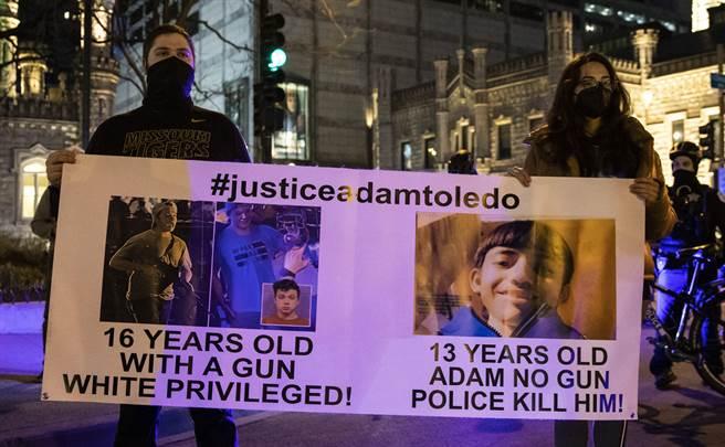 示威者舉牌抗議,芝加哥警方射殺舉起雙手的13歲墨西哥裔少年,但持槍的16歲白人少年卻沒事。(美聯社)