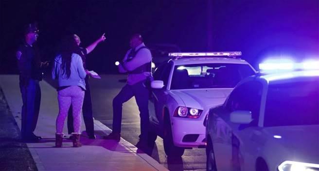 印第安納波利斯警方證實,該市的一處聯邦快遞大廈於當地時間15日23時,傳出槍擊案,至少8死。圖為警方封鎖道路,民眾向警察問路。(圖/美聯社)