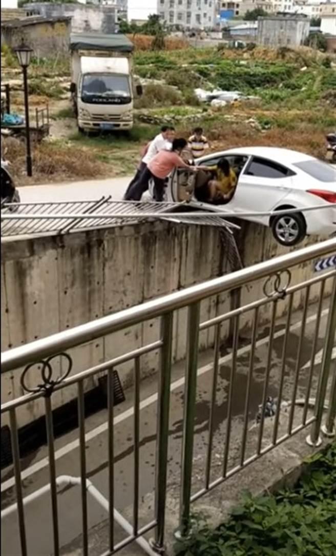 婦人倒車加速衝撞掉一旁的護欄,多虧路人即時出手相救才順利爬出車外。(圖/YOUTUBE)