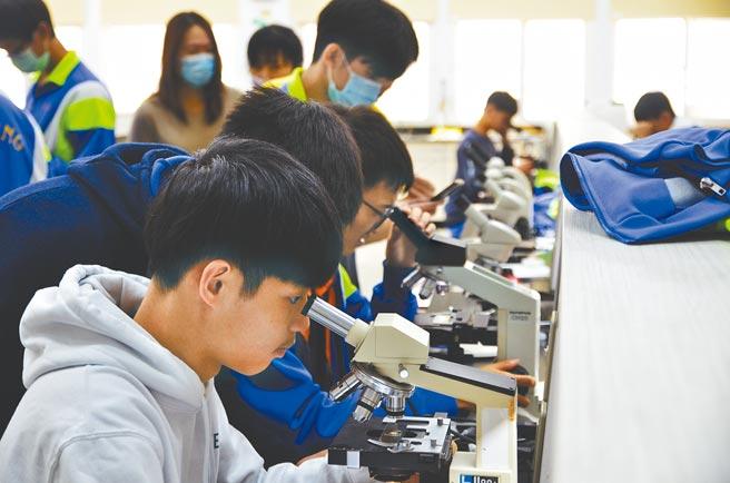 桃園市武陵高中特色必修課是「埤塘學」,學生透過顯微鏡認識埤塘多樣生物。(賴佑維攝)