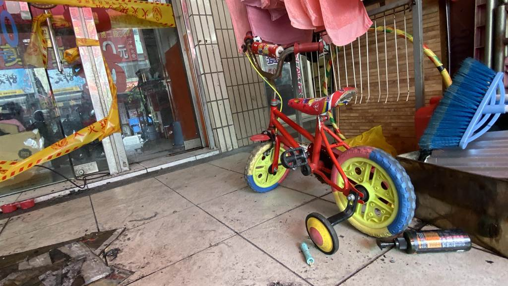 喪身火窟的易姓小兄妹阿公到火場前關心,指著火場前的兒童腳踏車說:「我兩個孫子都很喜歡騎這輛」。(陳淑芬攝)