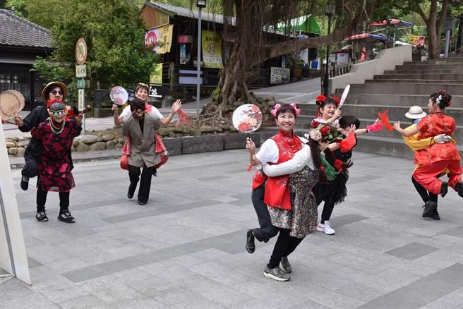 三义桐花祭安排游客跟着传统公背婆表演队伍一游桐花道。(谢明俊摄)