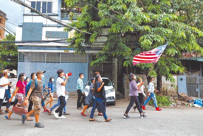 支持緬甸「民族團結政府」的民眾18日舉著聯邦旗幟在仰光街頭遊行,要求軍政府恢復民主制度。(路透)