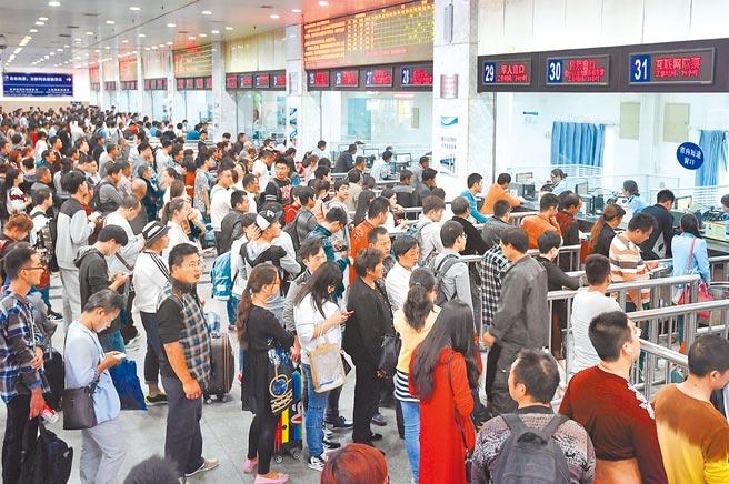 大陸業內人士分析,今年五一假期預料出遊人次將達2億人次。圖為鄭州火車站,民眾大排長龍等購票。(新華社)