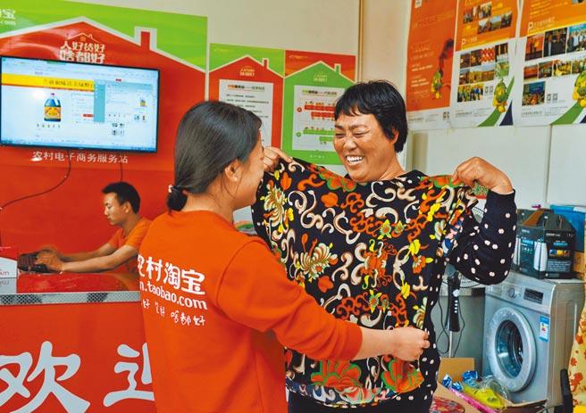 懂得鄉鎮居民的消費心態的人,成為各電商搶人對象。圖為河北村民在試穿網上購買的衣服。 (新華社)