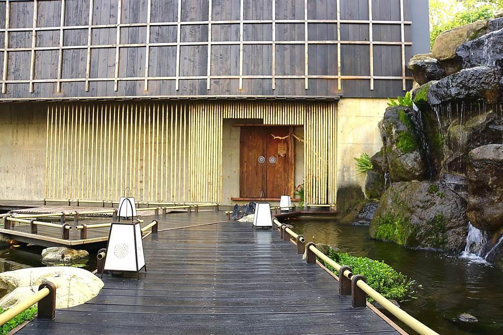 走进台中新餐厅〈飞花落院〉主建建筑,必须走过瀑布与水池相佐的木桥栈道,心境亦随之转换。(图/姚舜)