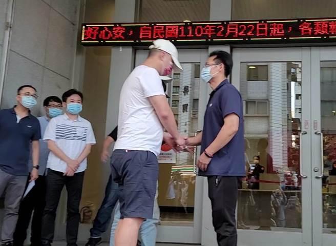 松山分局于22日傍晚召开记者会,找来杨姓警官与黑衣人握手言和,灰衣者为杨姓警官,白衣者为当时闹事的黑衣人。(林郁平摄)