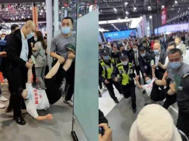 女車主在車展上跳上特斯拉電動車維權後,被保安拖走,還被上海公局處以5天拘留。(圖/網路)