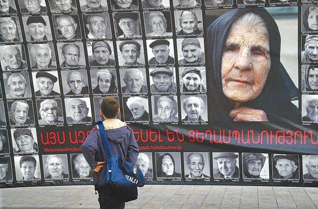 在亞美尼亞首都葉里溫街頭,一名男孩正觀看「亞美尼亞大屠殺」倖存者的照片。美國總統拜登預料會在24日宣布這場大屠殺為「種族滅絕」。(美聯社)