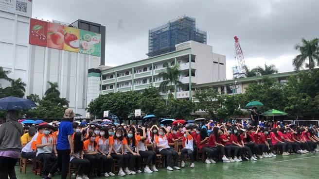 活動開始前現場突降大雨,集結於操場等待市長到來的學生,紛紛以雙手掩頭或脫下外套遮雨。(許哲瑗攝)