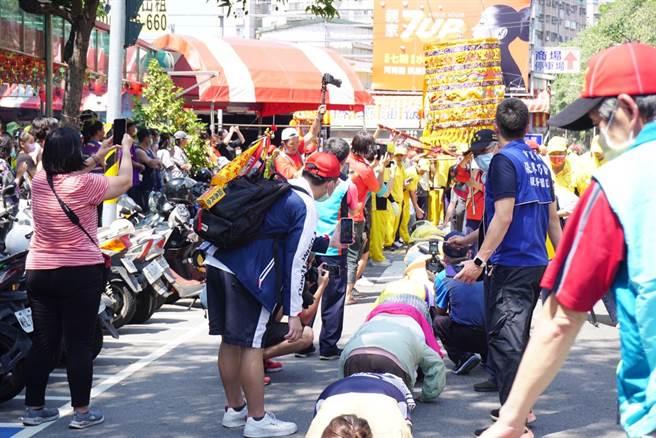台中萬和宮老二媽省親遶境,許多信眾趴在地上等候鑽轎腳。(萬和宮提供/林欣儀台中傳真)