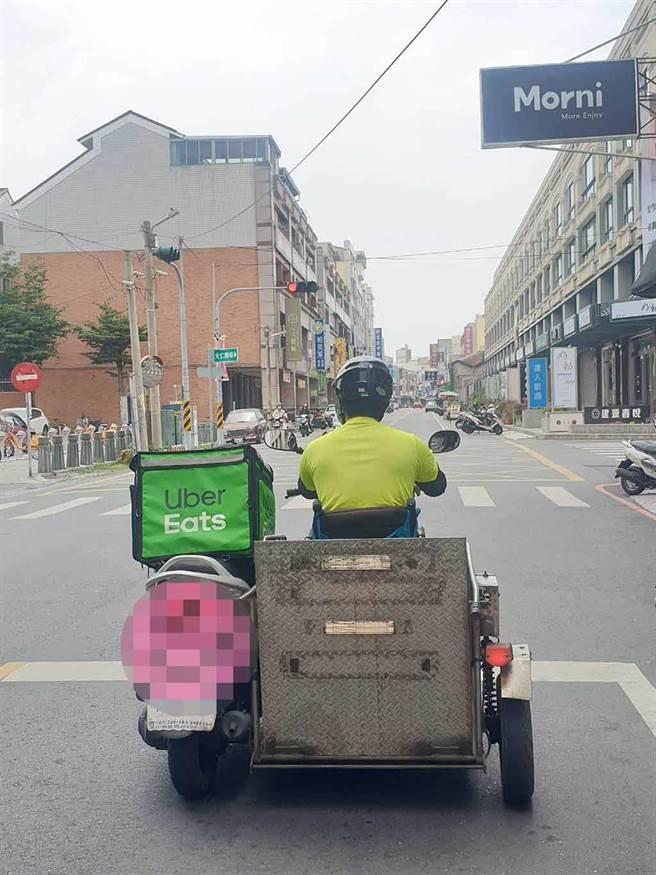 臉書「大員林生活圈」今天下午出現一張1輛輪椅改裝三輪摩托車正在停等紅燈的照片,但特別的是他旁邊掛著知名外送平台的保溫袋,吸引近千人留言按讚。(翻攝臉書「大員林生活圈」/吳建輝彰化傳真)