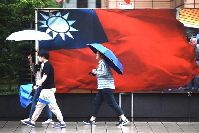 對流長出來了,西半部午後雷雨爆發。圖為台北街頭下起午後陣雨,路上行人紛紛撐起傘來。(陳信翰攝)