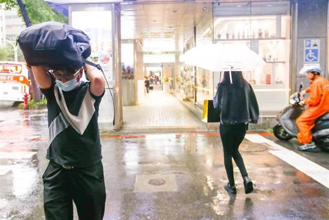27日台北街頭午後下起陣雨,民眾快速跑進騎樓裡。(鄧博仁攝)
