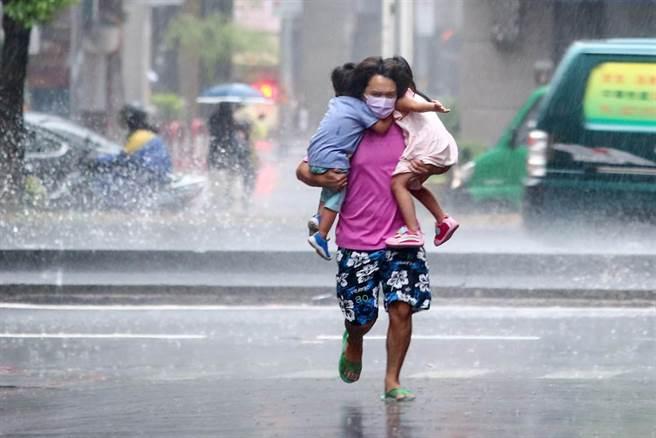 27日台北街頭午後下起陣雨,一位家長一手個抱一個小孩快速衝進屋內。(鄧博仁攝)