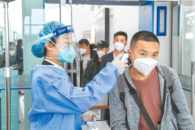 4月26日,在國際航站樓出境大廳,海關關員為旅客測量體溫。 (新華社)