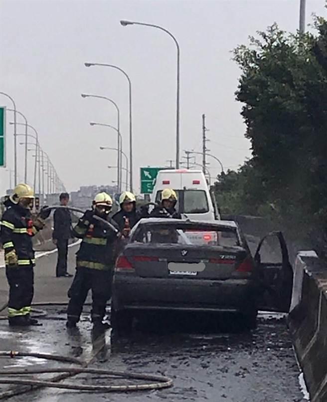 國1北向357.6公里楠梓出口28日上午8時20分發生一部小客車起火燃燒,消防人員到場撲滅火勢。(翻攝照片/林瑞益高雄傳真)