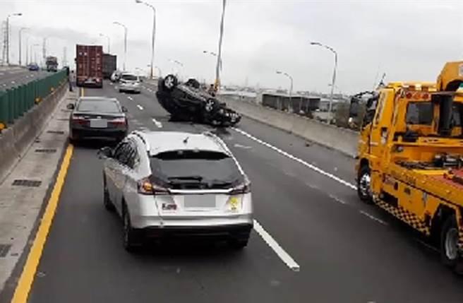 台61線車禍,賓士休旅車撞貨櫃車四輪朝天翻覆,其他車輛得從兩台車中間鑽縫過。(照片來源:記者爆料網)