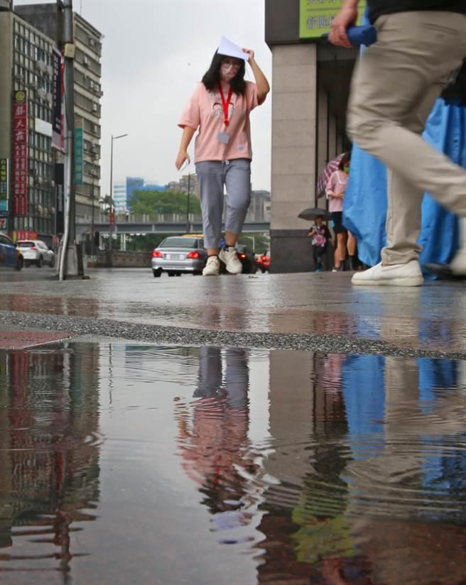隨著鋒面接近,28日早上開始台北市就出現短暫陣雨,路上行人用手遮雨跑向騎樓,市區雖有降雨積水但對水庫旱象仍無太大幫助。(陳君瑋攝)