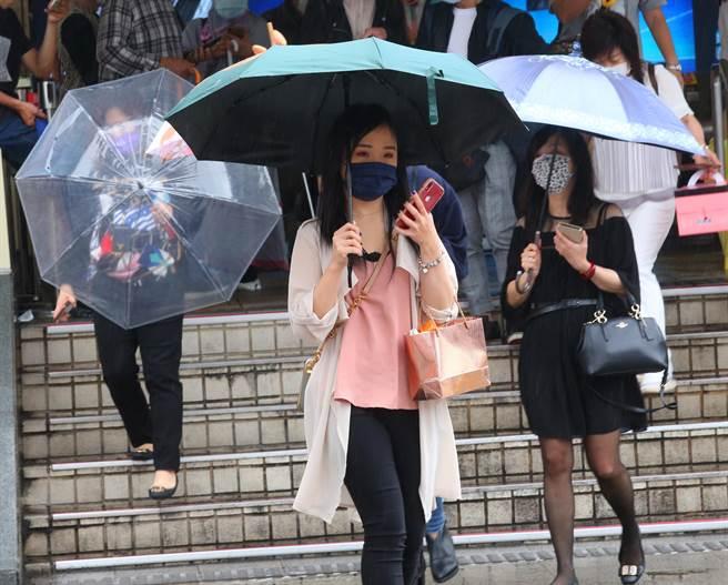隨著鋒面接近,28日早上開始台北市就出現短暫陣雨,路上行人紛紛撐起傘來遮雨。(陳君瑋攝)