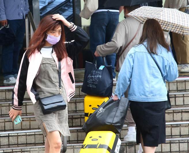 隨著鋒面接近,28日早上開始台北市就出現短暫陣雨,路上行人用手遮雨跑向騎樓。(陳君瑋攝)