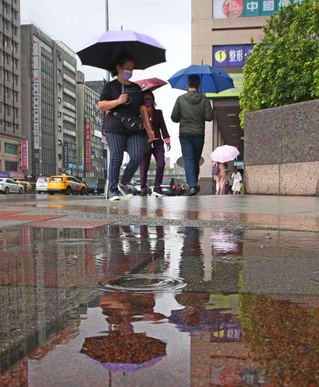 隨著鋒面接近,28日早上開始台北市就出現短暫陣雨,路上行人紛紛撐起傘來遮雨,市區雖有降雨積水但對水庫旱象仍無太大幫助。(陳君瑋攝)