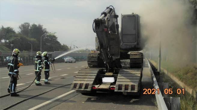 一部曳引車載運怪手,1日上午7時44分許,於國道1號南向363.4公里鼎金路段起火,消防人員到場搶救。(翻攝照片/林瑞益高雄傳真)