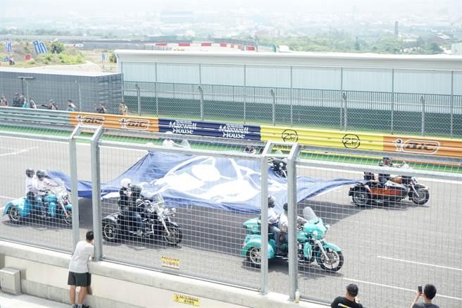 6位哈雷重機騎士手持7乘10的FIA藍色大旗,象徵全球最高等級賽車運動的國際組織認可麗寶賽道。(王文吉攝)