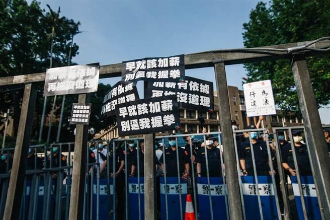 工會成員在拒馬上黏貼「加薪有依據 再拖沒道理」貼紙,表達訴求,警方則舉起行為違法警告牌,喝令解散。(郭吉銓攝)