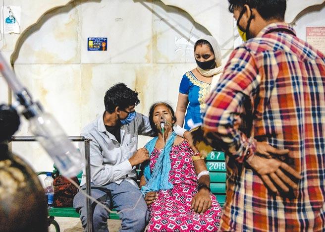 印度新冠疫情嚴峻,連日寫下新增確診紀錄,呼吸器和氧氣機大缺貨。一名女性患者在北部城市加濟阿巴德的錫克教謁師所,用力吸取免費氧氣。(路透)
