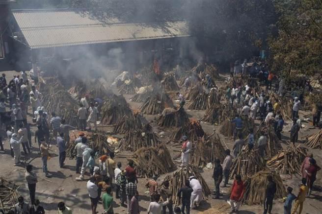 圖為印度新德里日前對不幸感染新冠病毒過世的民眾,就地進行火化。(美聯社)