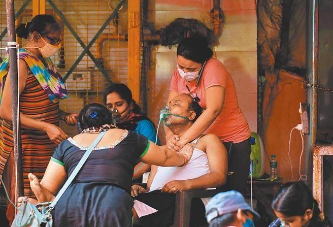 印度疫情持續惡化導致醫療物資缺乏,尤其急缺氧氣。圖為一名新冠肺炎患者呼吸困難,他的家人幫忙按摩他的胸口。(路透)