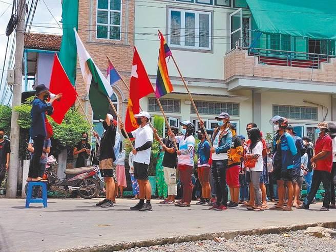 緬甸軍事政變逾3個月 安全部隊開槍至少8死。圖為日前在緬甸,一場抗議軍事政變的示威者高舉旗幟。(資料照/路透)