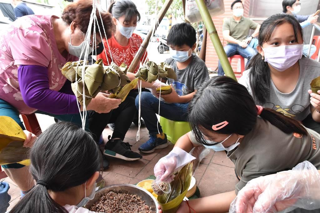 50名家政媽媽帶領50名國小學童包鳳梨粽,小朋友們包了還想再包。(周麗蘭攝)