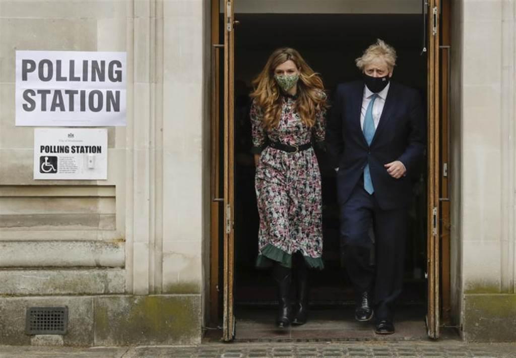 英國舉行脫歐及新冠疫情爆發以來的首次地方和區域選舉。圖為英相強生與女友席孟茲一同走出投票所。(圖/美聯社)