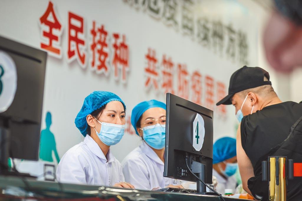 大陸醫護人員為接種疫苗的市民登記信息。(新華社)